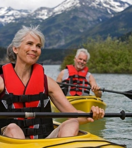 Active senior man and woman in kayaking with the mountains in the background