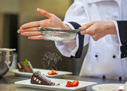 Female chef finishing a dessert plate