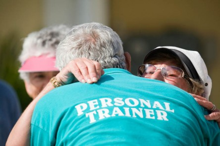Personal trainer hugging senior woman at an event