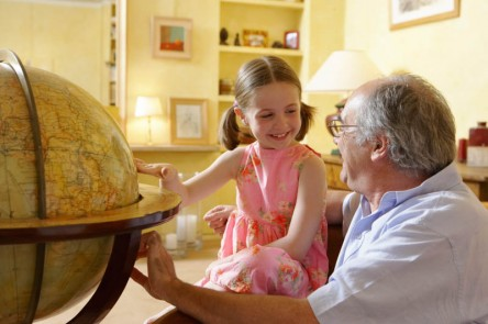 Grandfather and granddaughter studying a globe
