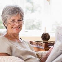 Woman in living room reading newspaper smiling to camera