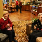 Mrs. S and Mrs. S were enjoying a wonderful drink by the warm fireplace.
